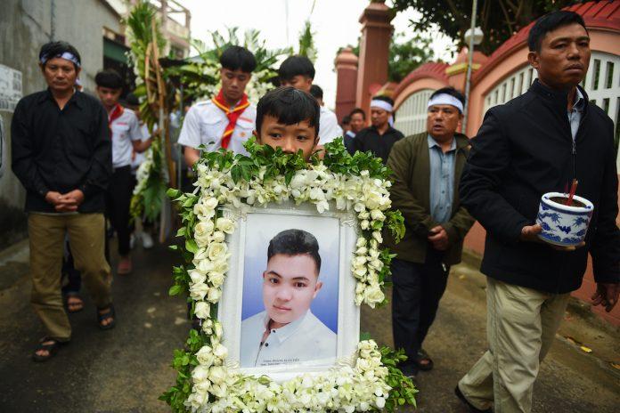 A family member carries a portrait Hoang Van Tiep