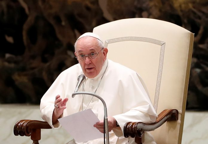 Pope Francis giving address behind microphone