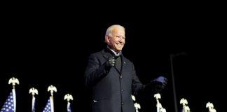 Joe Biden in front of American flags, black background | Licas News
