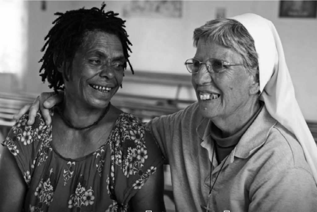 Black and white photo of Sister Lorena Jenal with a victim of sorcery accusation violence.