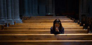 One woman praying in empty church
