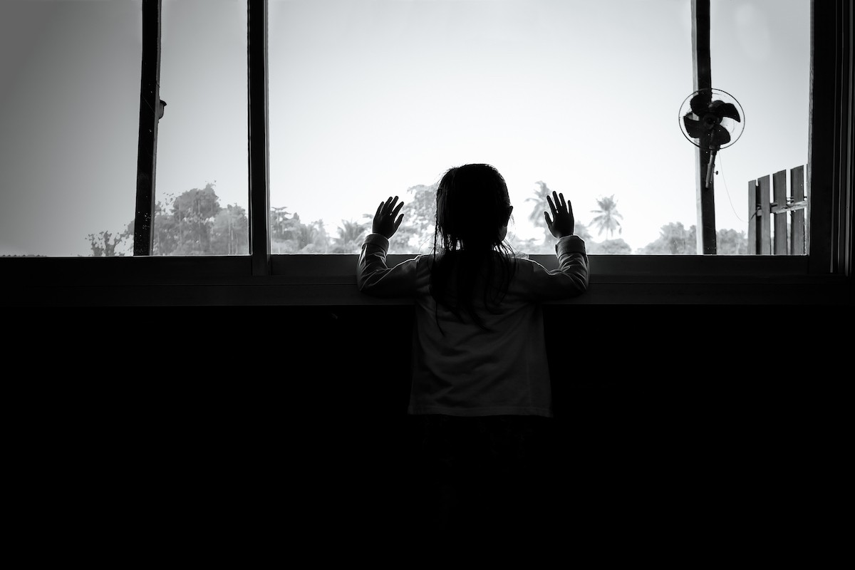 Black and white photo of back of child looking out of a large window