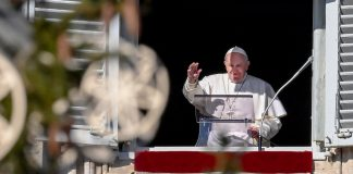 Pope Francis waves from apostolic palace overlooking St. Peter's Square during the weekly Angelus prayer on Dec. 13, in the Vatican.