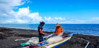 Fishermen fix their nets on the shore