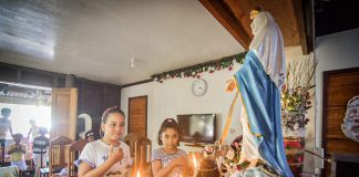 Children join a family prayer before the image of the Blessed Virgin Mary