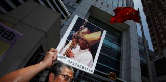 A protester carries a portrait of Bishop Su Zhi-ming of Baoding, Hebei province