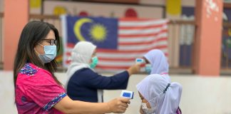 Students have their temperature taken at a school in Malaysia
