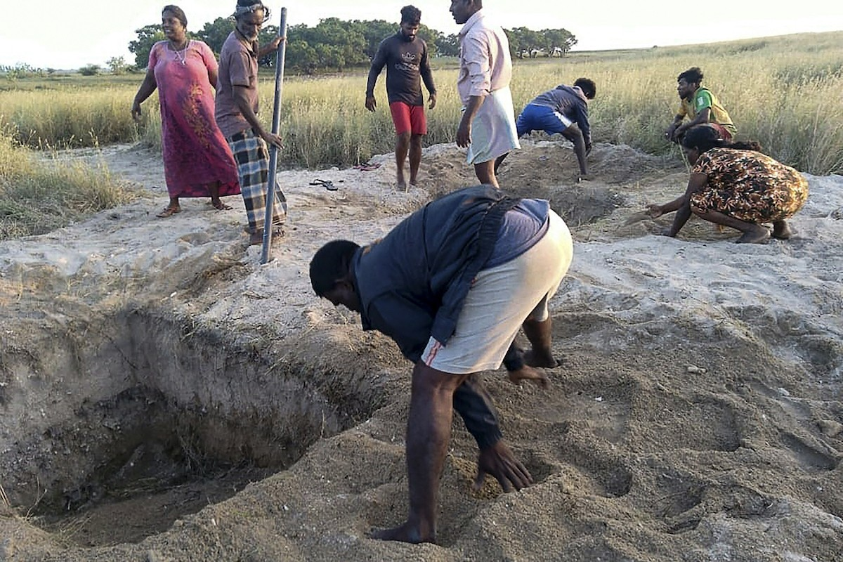 Local residents in Sri Lanka try to fill the graves dug by the authorities to bury COVID-19 victims