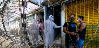 Malaysian health worker in PPE behind barbed wire fence | LiCAS.news