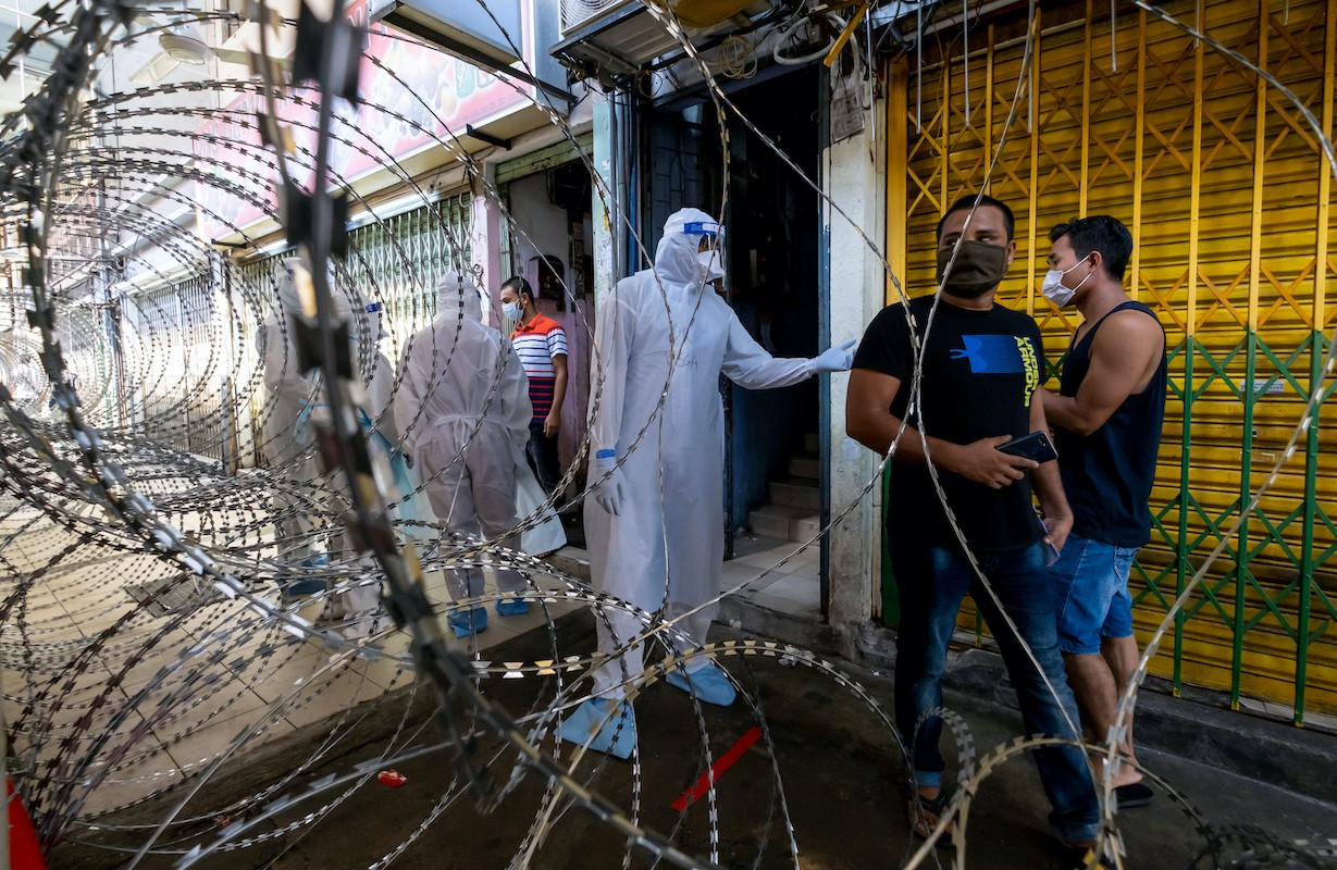 Malaysian health worker in PPE behind barbed wire fence   LiCAS.news