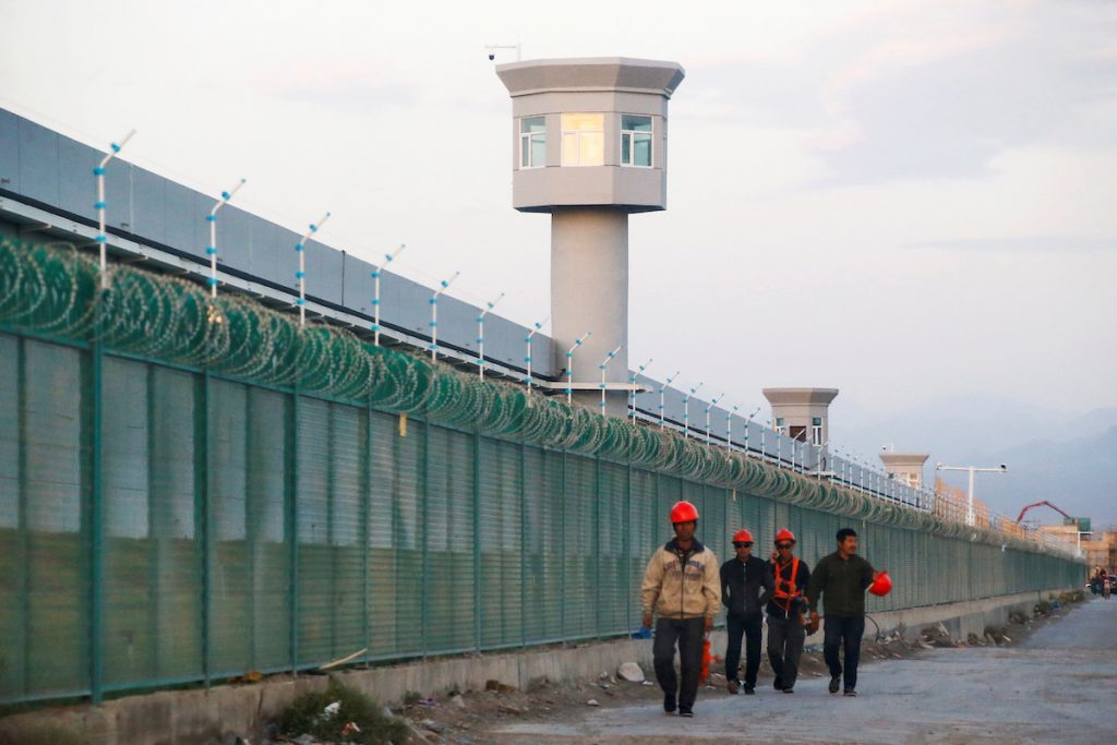 Workers walk by the perimeter fence in Xinjiang