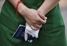 Nurse in green overall holding blue passport