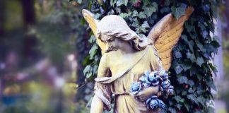 Vintage image of a sad angel against the background of leaves (fragment)