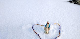 Statue of Virgin Mary and Rosary with snow in the background at the top of Mount Everest