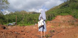 A nun standing among cyclone desvasted landscape | LiCAS.news