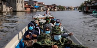 Government workers and policemen ride a boat to the island of Tibaguin, Philippines